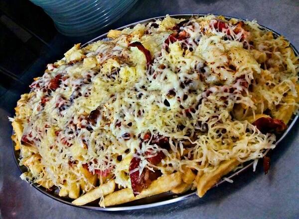 Porção de batata frita com queijo e bacon